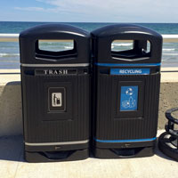 Trash and mixed recycling containers on beach front