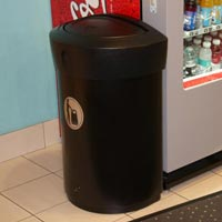Half-moon Envoy™ 29G Trash Can indoors at gas station