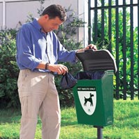 Man disposing of a dog poop bag in the Fido Pet Waste Station